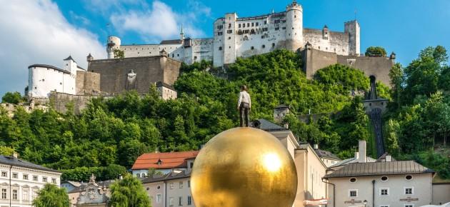 Über der Salzburger Altstadt thront deren Wahrzeichen, die Festung Hohen Salzburg. Davor ein Kunstwerk von Stephan Balkenhol.